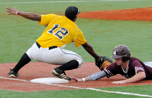 Hinds Community College's Toler Robinson (right) dives back to first before Pasco-Hernando State College's Joel Rosario can tag him during the NJCAA Division II World Series at David Allen Memorial Ballpark Tuesday, May 27, 2014. (Staff Photo by BONNIE VCULEK)