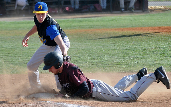 Pioneer's Carter Postier dives back into first base ahead of tag from Drummond's Parker Jankey Thursday during a regional playoff game at Pioneer High School. (Staff Photo by BILLY HEFTON)