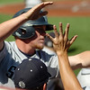 SWOSU's J. R. Head celebrates the Bulldogs' first run with his teammates after scoring against the University of Arkansas-Monticello during the Great American Conference Championship Tournament at David Allen Memorial Ballpark Saturday, May 3, 2014. (Staff Photo by BONNIE VCULEK)