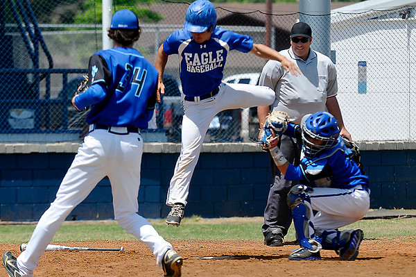 Hennessey's Steven Lott tries to leap over Union City catcher Rance Lewman as pitcher Josh McMian backs up the play Saturday during the championship game of the regional tournament at Hennessey High School. (Staff Photo by BILLY HEFTON)