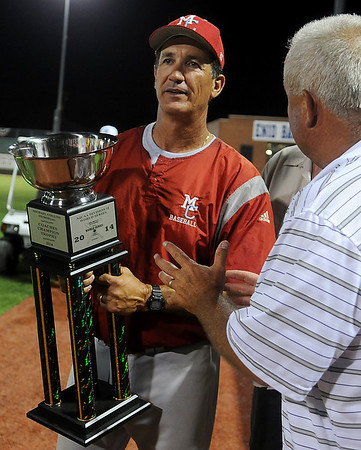 Steve Winterling (left), Mesa Community College's head baseball coach, holds the Michael Collins Memorial Coaches Champion Trophy after accepting the award from Bill Mayberry. The Thunderbirds won the NJCAA Division II World Series at David Allen Memorial Ballpark in Enid, Okla. Saturday, May 31, 2014. (Staff Photo by BONNIE VCULEK)