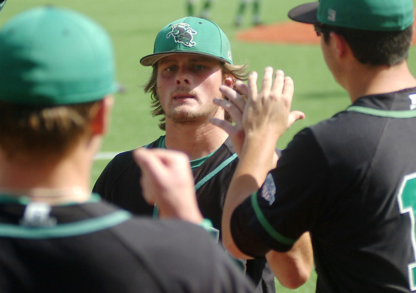 UAM's Kade Garlington (center) receives congratulations as he returns to the Boll Weevils dug out during the Great American Conference Championship game at David Allen Memorial Ballpark Tuesday, May 6, 2014. (Staff Photo by BONNIE VCULEK)