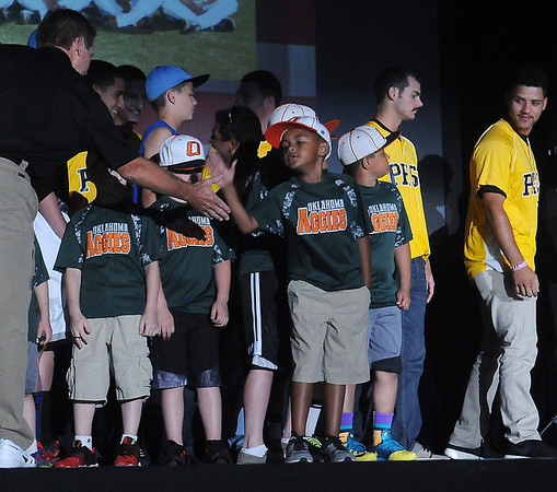 The Pasco-Hernando State Conquistadors' head coach high-fives the Oklahoma Aggies players as the teams NJCAA Div. II World Series teams are introduced during a rally at the Enid Event Center Friday, May 23, 2014. (Staff Photo by BONNIE VCULEK)
