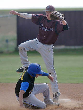 Pioneer's Kade Cronkhite steps over Garrett Menendez of Drummond after throwing to first for a double play Thursday during a regional playoff game at Pioneer HIgh School. (Staff Photo by BILLY HEFTON)