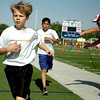 Eisenhower Elementary School's Brian Higbee (left) and Joseph Rodriguez finish one/two as Coach Steve Bloom checks the runners' times in the 800 meter run during Little Olympics at D. Bruce Selby Stadium Wednesday, May 7, 2014. (Staff Photo by BONNIE VCULEK)