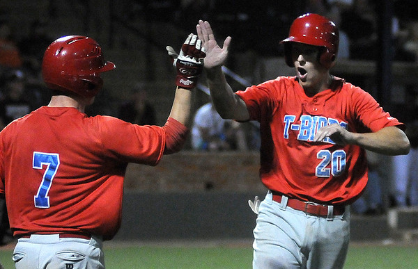 Mesa Community College's Jordan Zimmerman (right) celebrates his score with Zack Soria during the Thundebirds 9-7 win over Hinds in the NJCAA Division II World Series championship game at David Allen Memorial Ballpark Saturday, May 31, 2014. (Staff Photo by BONNIE VCULEK)
