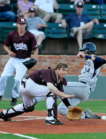 Mike Jordahl of Madison College slides into home aheads of a tag from Hinds CC's Jonathan Washam Wednesday during the NJCAA DII World Series at David Allen Memorial Ballpark. (Staff Photo by BILLY HEFTON)