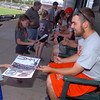 NOC Enid's Dyce Applegate hands back a signed poster to Gage Tennyson during an autograph session at David Allen Memorial Ballpark Wednesday. (Staff Photo by BILLY HEFTON)