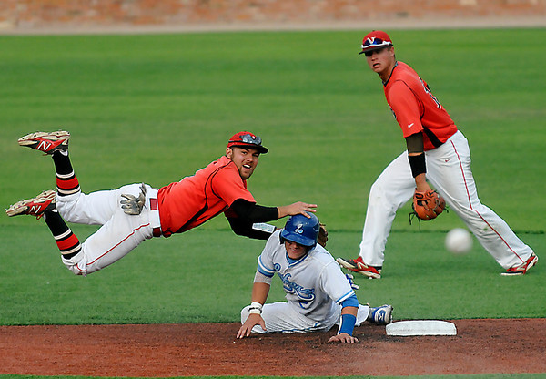 NOC Enid's Dyce Applegate is upended by Longview's Colton Hilbrenner after taker a throw by Nick Yoning during the Plains District Tournament Friday at David Allen Memorial Ballpark.  (Staff Photo by BILLY HEFTON)