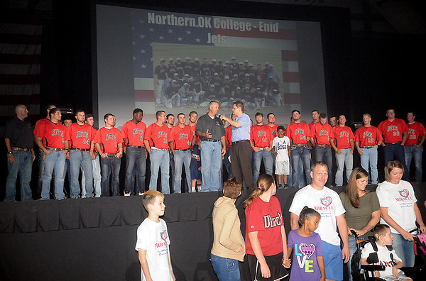 Northern Oklahoma College Enid Jets appear on stage as head coach Raydon Leaton (center) discusses their season during the National Junior College Athletic Association Division II World Series rally at the Enid Event Center Friday, May 23, 2014. Miracle League players (front) are the Jets hosts during the week. (Staff Photo by BONNIE VCULEK)