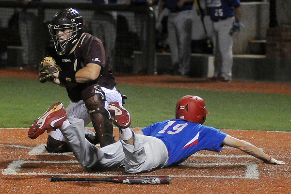 Lincoln Land Community College's Tyler Borski slides across the plate before Hinds Community College's Caleb Upton can make the tag during game 4 of the NJCAA Division II World Series at David Allen Memorial Ballpark Saturday, May 24, 2014. (Staff Photo by BONNIE VCULEK)