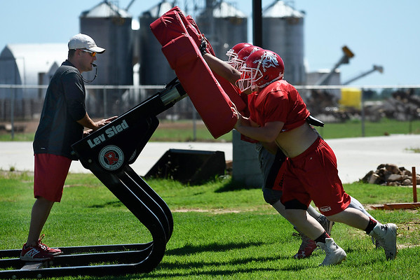 Kremlin-Hillsdale assistant football coach, Pete Voth, rides a blocking sled as players go through drills during spring practice Wednesday May 17, 2017. (Billy Hefton / Enid News & Eagle)