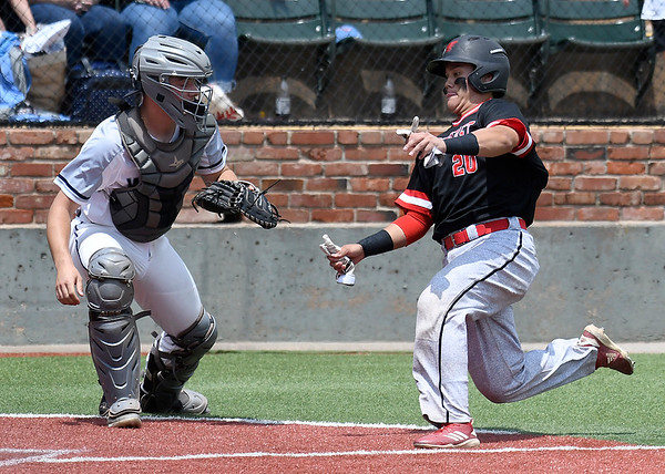 Northeast CC's Bryce Walker scores pass Madison College's Lucas Trebian during the NJCAA DII World Series Monday May 27, 2019 at David Allen Memorial Ballpark. (Billy Hefton / Enid News & Eagle)
