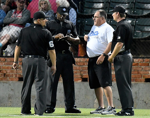 New World Series director, Lind Hartsell, visits with umpires about a weather delay in the NOC Enid v Kellogg game Saturday May 25, 2019. (Billy Hefton / Enid News & Eagle)