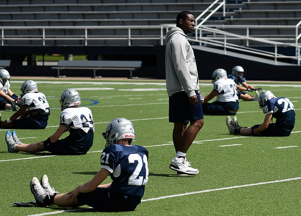 Enid head coach , Rashaun Woods, walks among his playes as they warm-up during spring practice Tuesday May 21, 2019 at D. Bruce Selby Stadium. (Billy Hefton / Enid News & Eagle)