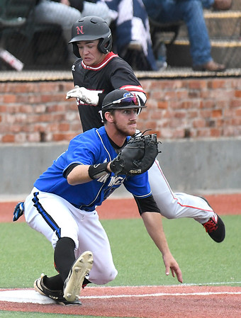 Carl Albert CC's Lane Grogan waits on the ball as NOC Enid's Brendon Woelfle beats the throw for a base hit during the Region 2 tournament Friday May 10, 2019 at David Allen Memorial Ballpark. (Billy Hefton / Enid News & Eagle)