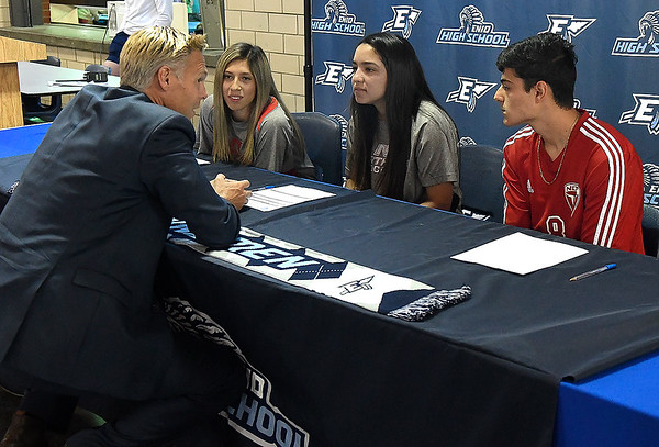 Enid head soccer coach, Craig Liddell, talks to (left to right) Nadia Chavez, Janet Moreno and Ivan Delgadillo prior to the trio signing letters of intent to play soccer for NOC Tonkawa during a ceremony at Enid High School Thursday May 16, 2019. (Billy Hefton / Enid News & Eagle)