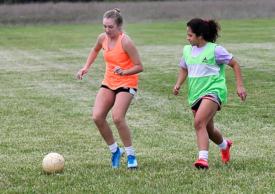 Marissa Neil (left) and Andrea Rivera during practice of the Enid Varsity team Friday, May 15, 2020. (Billy Hefton / Enid News & Eagle)