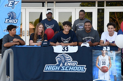 Cyson Mathis (center) signing a letter of intent to play basketball at Oklahoma Wesleyan University  on the steps of the new Enid High School gym Friday, May 29, 2020. He is flanked by his brother, Cash and mother, Mandy (left) and his father, Chris and brother Cam (right) and Enid head coach Curtis Foster and Marcus Odom (behind). (Billy Hefton / Enid News & Eagle)