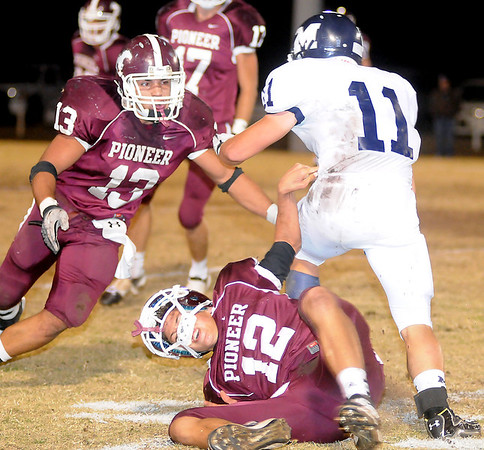 Pioneers'  Jett Jobe slows up Minco's Tyler Mitchum as Aaron Chain zeros in for the tackle Friday at Mustang Field. The Minco Bulldogs led the Pioneer Mustangs 20-7 at the half. (Staff Photo by BONNIE VCULEK)