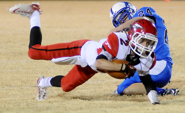 Washington's Brady Kulbeth dives forward for extra yardage as Hennessey's William Arndt makes the tackle during the 2A second round playoff game at Hennessey High School Friday. (Photo by BONNIE VCULEK, Enid News and Eagle)