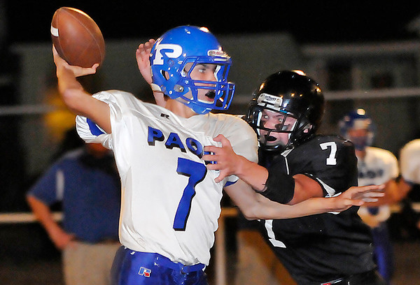 Pond Creek-Hunter's Trenton Grimes pressures Paoli quarterback, D.J. Moore, Friday during the first round of the class B state playoffs at Pond Creek. (Staff Photo by BILLY HEFTON)
