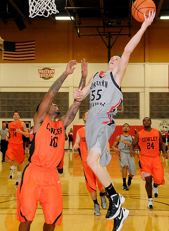 NOC Enid Jets' Connor Brooks scores on a fast break against Cowley County Tigers' James Milliken Thursday at the Mabee Center. (Staff Photo by BONNIE VCULEK)