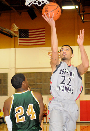 NOC Enid Jets' Jeremy Espinoza lays the ball in against Oklahoma Baptist University Junior Varsity's Marques Jackson Tuesday at the Mabee Center. The Jets had a commanding 48-12 lead at the half. (Staff Photo by BONNIE VCULEK)