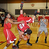 Bacone College JV's Jon Colunga dives head-first over NOC-Enid Jets' Philip Brown as the players scramble for the rebound Thursday during the Jets' basketball season opener at the Mabee Center. (Staff Photo by BONNIE VCULEK)