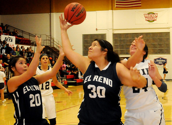 El Reno's Lexus Halfred (center) grabs an offensive board against Enid's Grace Enmeier (right) during the Pacers' 50-45 win over the Lady Indians Thursday at Northern Oklahoma College-Enid's Mabee Center. (Photo Courtesy of Enid News and Eagle, Bonnie Vculek)