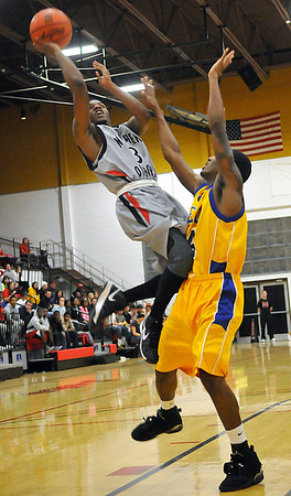 NOC's Kyndall Dudley puts up a shot against Terrence Clemens of NEO Monday at the Mabee Center. (Staff Photo by BILLY HEFTON)