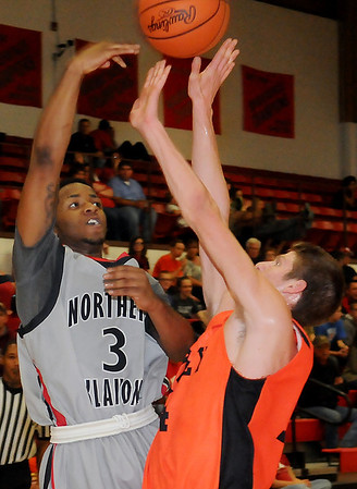 NOC Enid Jets' Kyndall Dudley passes the ball over the outstretched arms of Cowley County Tigers' Ben Vozolla Thursday at the Mabee Center. (Staff Photo by BONNIE VCULEK)