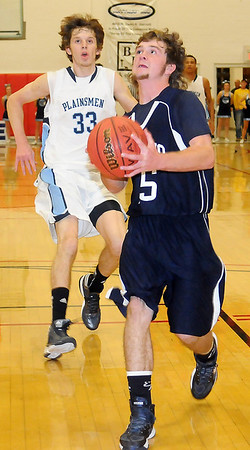El Reno's Bailey Denny breaks away for a score against Enid's Michael Major Thursday during the Indians 56-49 win over the Plainsmen at Northern Oklahoma College-Enid's Mabee Center. (Photo Courtesy of Enid News and Eagle, Bonnie Vculek)