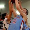Chisholm's Caleb Lang (12) grabs a rebound against Pioneer's Sage Lamunyon (5) Friday at Pioneer High School. (Staff Photo by BONNIE VCULEK)