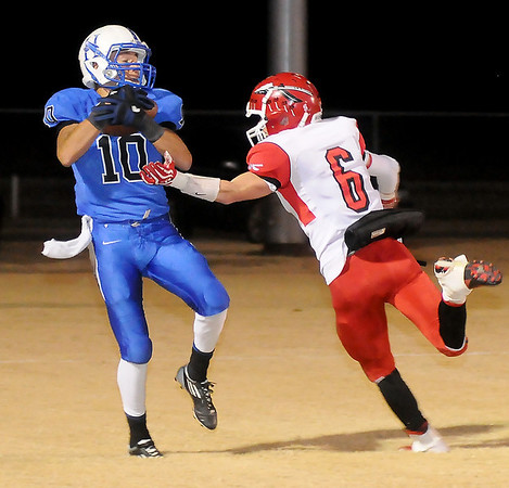 Hennessey's Edgar Fierro catches a touchdown pass from Dylan Hatchel as Washington's Bo Nixon defends Friday during the 2A state football playoffs at Hennessey High School. (Staff Photo by BONNIE VCULEK)