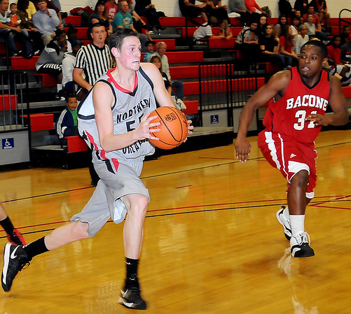 NOC-Enid Jets' Connor Brooks drives the baseline against Bacone College JV's Darrius Patterson Thursday during the Jets' basketball season opener at the Mabee Center. (Staff Photo by BONNIE VCULEK)