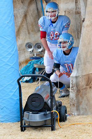 Okeene's Cade Mitch and Drew Nault take advantage of a sideline heater Saturday during the second round of the class A state playoffs. (Staff Photo by BILLY HEFTON)