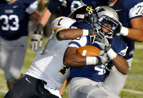 Enid's Raheem Mitchell is collared by Tre Betts of Sand Springs Friaday at D. Bruce Selby Stadium. (Staff Photo by BILLY HEFTON)