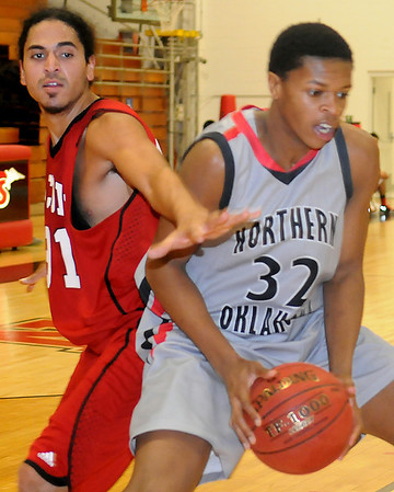 NOC Jets' Jordan Evans fights for position under the bucket for a shot against Bacone JV's Eric Jones during the Jets' 126-50 win at the Mabee Center Wednesday, Nov. 13, 2013. (Staff Photo by BONNIE VCULEK)