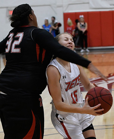NOC Enid's Macie Jo Pierce is fouled by Oklahoma Elite's Vanesea Bledsoe as she drive to the basket Tuesday November 14, 2017 at the NOC Mabee Center. (Billy Hefton / Enid News & Eagle)