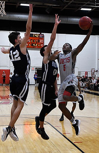NOC Enid's Dyaire Holt drives to the basket against OKC Storm's Tyson Anderson and Mason Turner Tuesday November 14, 2017 at the NOC Mabee Center. (Billy Hefton / Enid News & Eagle)
