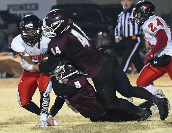 Pioneer's Kalen Smith and Kaleb REddick combine to stop Turpin's Cesar Anchondo during the opening round of the class B playoffs Friday November 10, 2017 at Pioneer High School. (Billy Hefton / Enid News & Eagle)