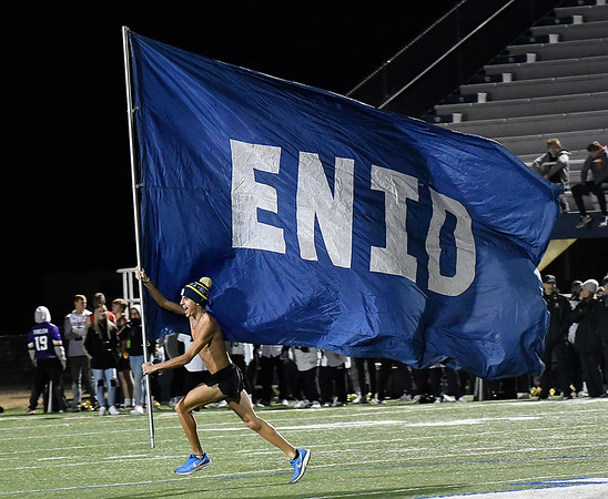 An Enid student proudly carries the school flag after a touchdown against Broken Arrow Friday, November 8, 2019 at D. Bruce Selby Stadium. (Billy Hefton / Enid News & Eagle)