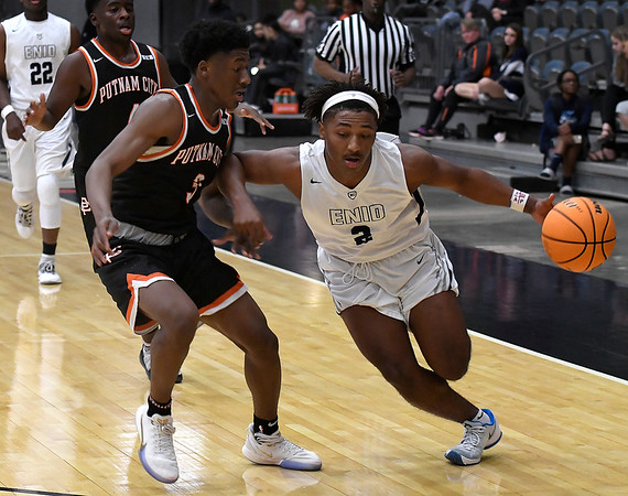 Enid's Telin Phillips drives towards the basket against Putnam City's Kendural JollyTuesday, November 26, 2019 during the home opener at the Stride Bank Center. (Billy Hefton / Enid News & Eagle)