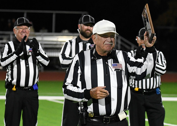 Richard Parker acknowledges the crowd after recieving a plaque prior to his final game as a referee after 58 years Friday, November 8, 2019 at Pond Creek-Hunter High School. (Billy Hefton / Enid News & Eagle)