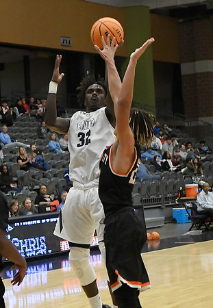 Enid's Mason Berry shoots over Putnam City's N'Kozi Harris Tuesday, November 26, 2019 during the home opener at the Stride Bank Center. (Billy Hefton / Enid News & Eagle)