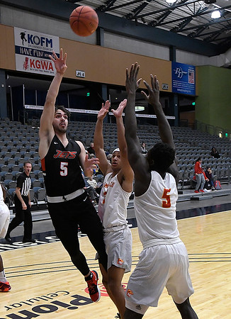 NOC Enid's Zach McDermott shoots over New Mexico's Rafael Jenkins and Gideon George Thursday, November 14, 2019 during the NOC/Chick-fil-A Classic at the Stride Bank Center in Downtown Enid. (Billy Hefton / Enid News & Eagle)