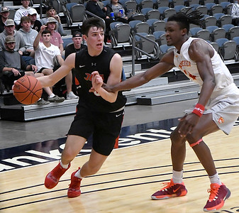 NOC Enid's Andrew O'Brien drives to the basket against New Mexico's Keaton Hervey Thursday, November 14, 2019 during the NOC/Chick-fil-A Classic at the Stride Bank Center in Downtown Enid. (Billy Hefton / Enid News & Eagle)