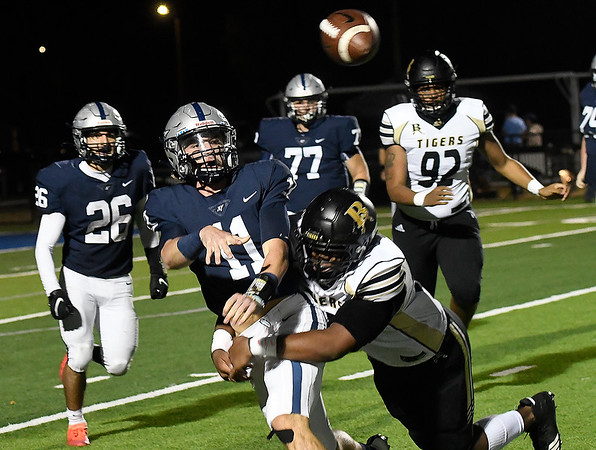 Enid's Blake Priest throws a pass while being tackled Broken Arrow's Migeul Trejo Friday, November 6, 2020 at D. Bruce Selby Stadium. (Billy Hefton / Enid News & Eagle)