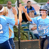 Enid Pacers' Kaitlin Bell (right) receives congratulations from her teammates Courtney Chelf and Haven Bay after Bell scores giving the Pacers a 5-0 lead over the Woodward Boomers in the bottom of the first inning Monday at Pacer Field. (Staff Photo by BONNIE VCULEK)